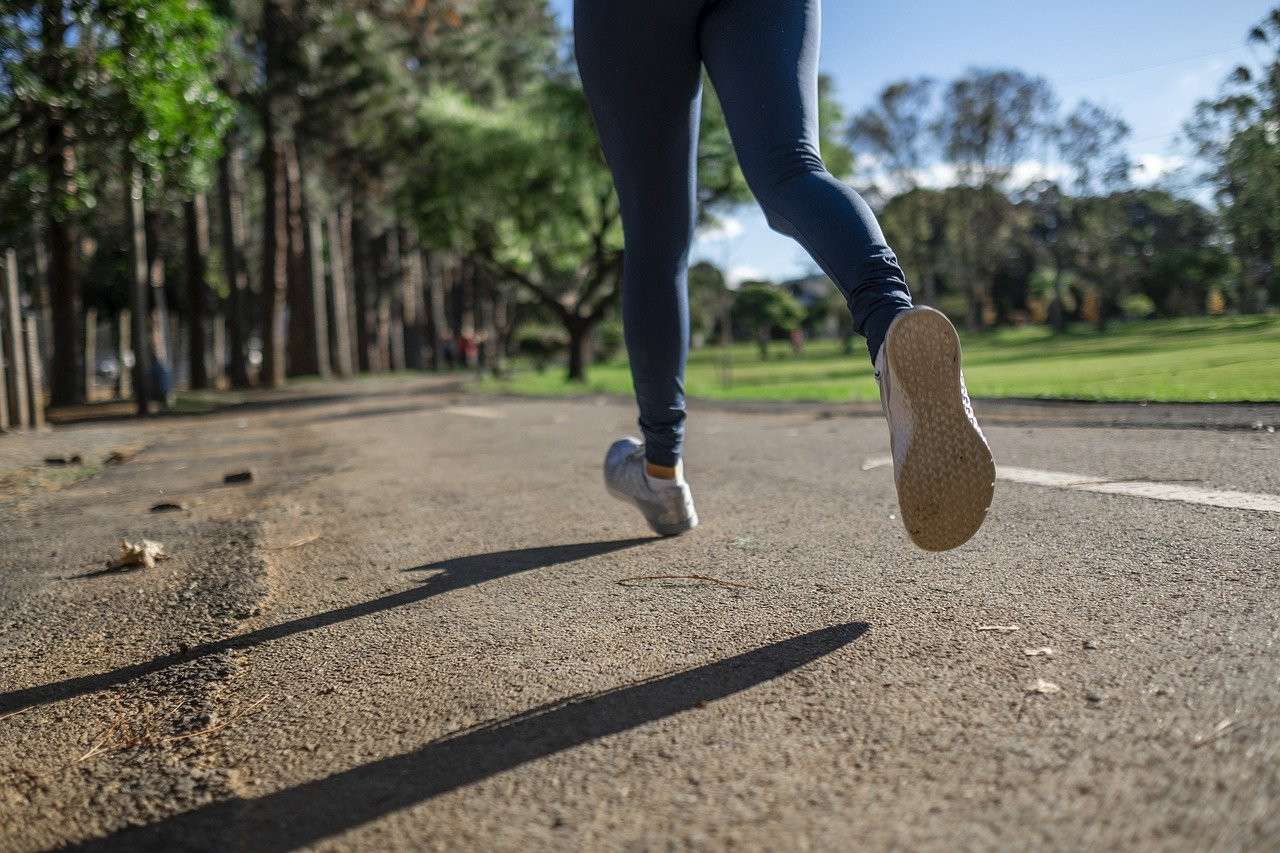 Legs and feet of an athlete running down a road in a green park surrounded by trees.