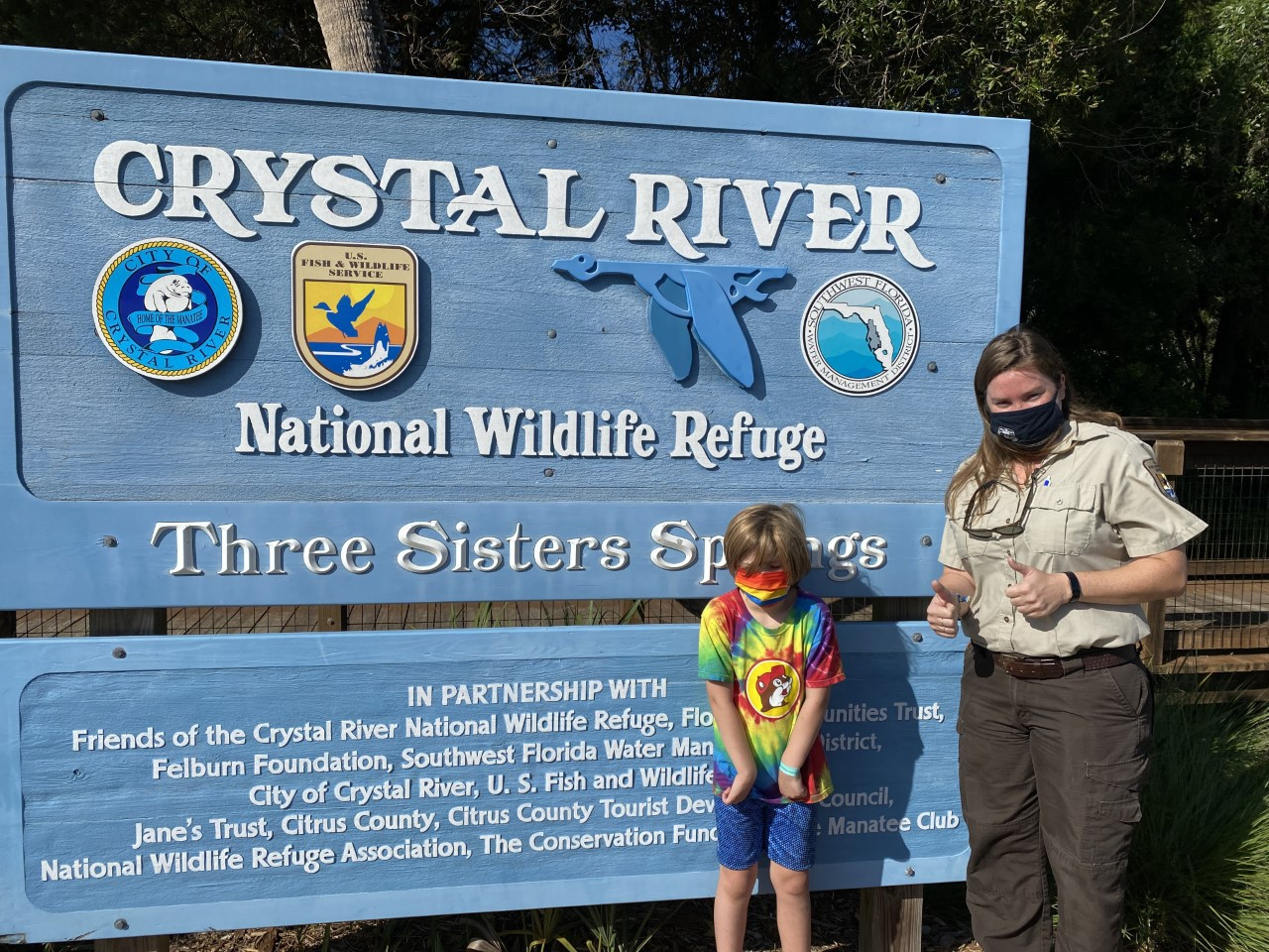 woman in FWS uniform flashing 2 thumbs up next to kid in tie-dye T-shirt in front of Crystal River National Wildlife Refuge sign