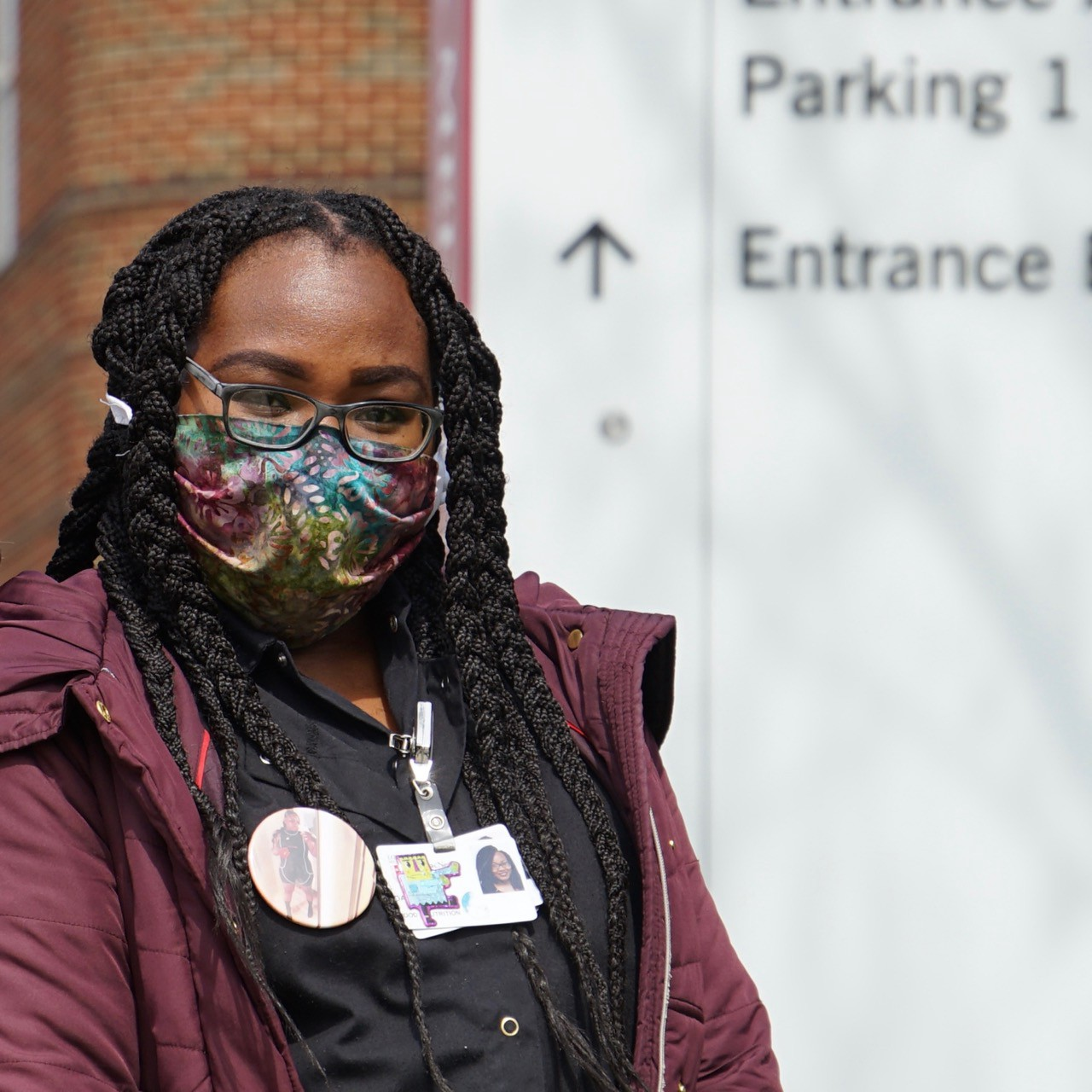 A hospital worker stands in front of the parking lot sign outsider her workplace.