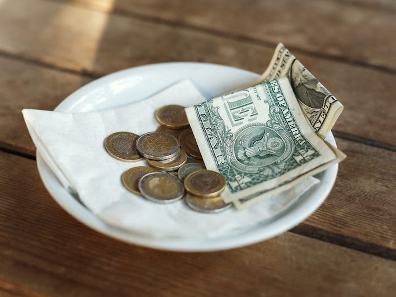 Money on a plate that was left as a tip.