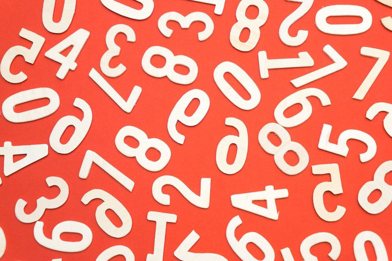 An assortment of white cut-out numbers on a red background
