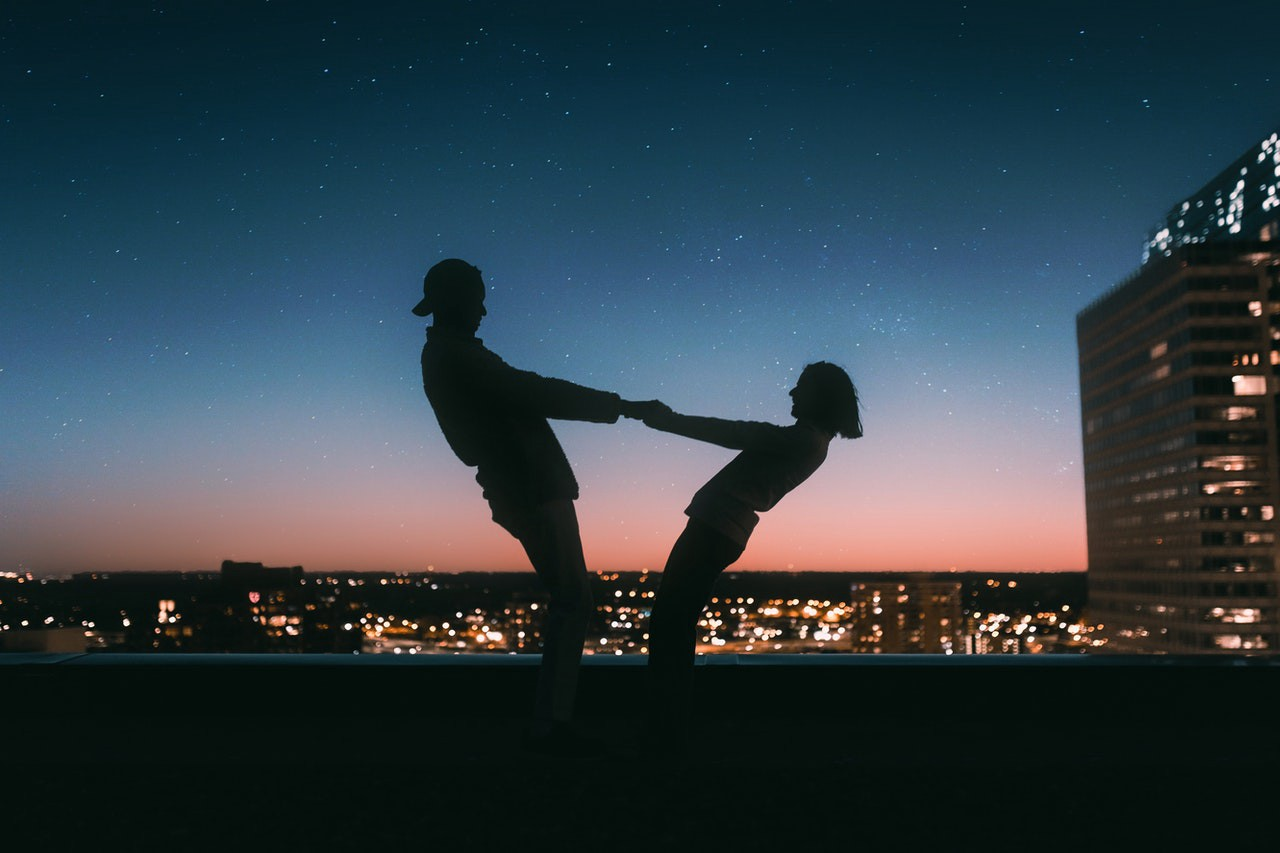 boy and girl standing on rooftop at dusk
