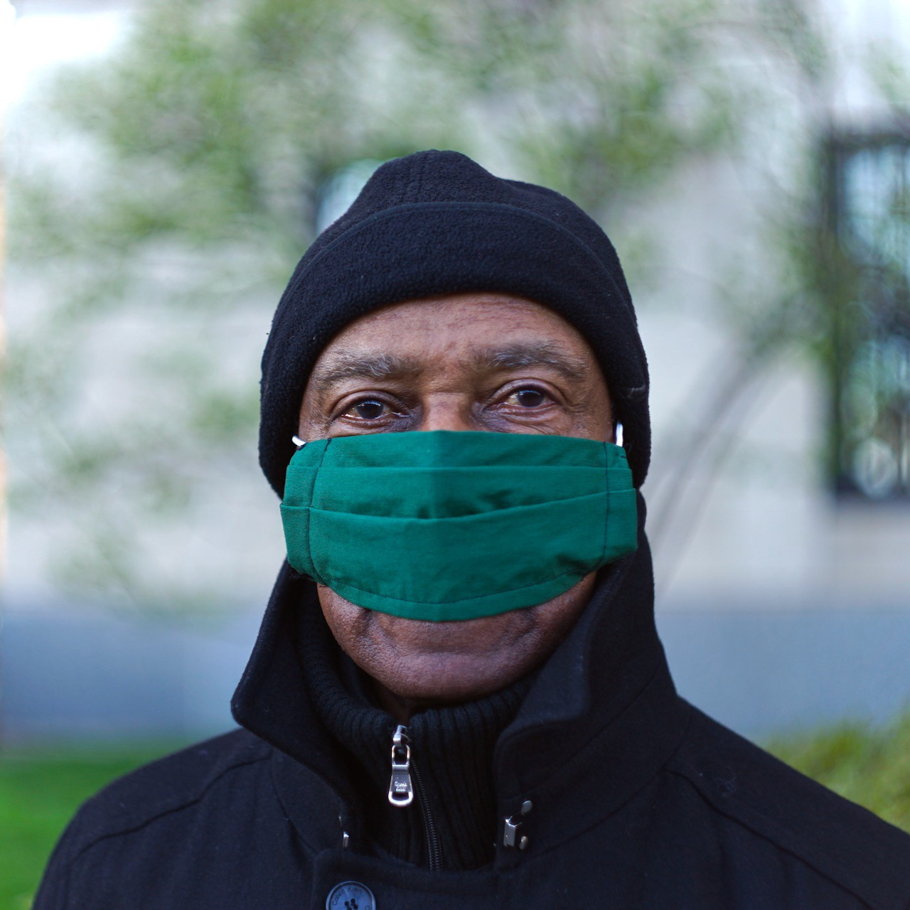 A man with a black hat and a narrow green mask.