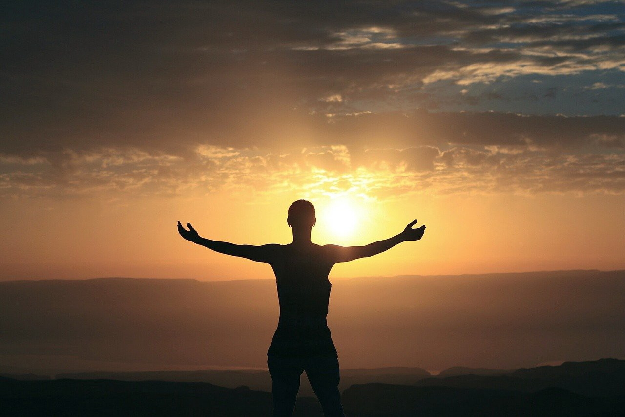 woman, facing the sunrise, engaged in gratitude practice