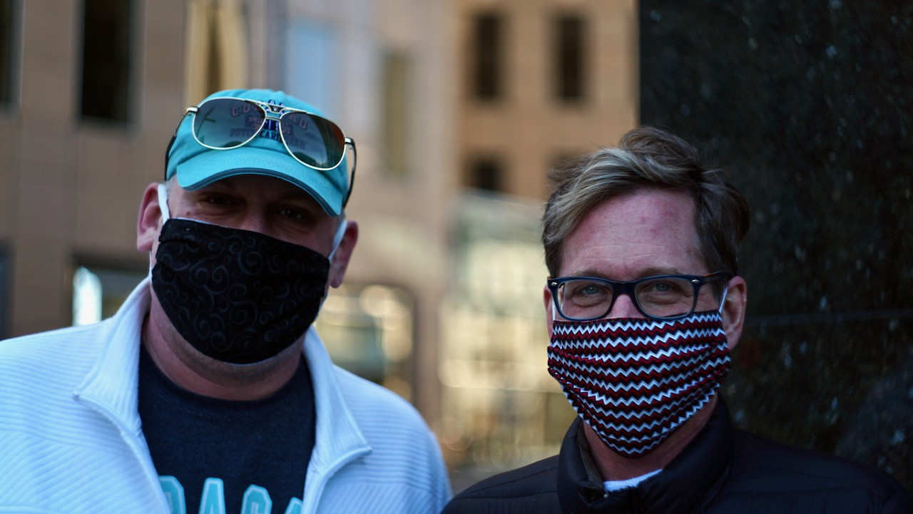 Two men exiting an apartment building show off their masks.