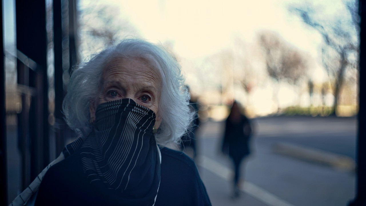 An elderly woman wears a mask improvised from a scarf.