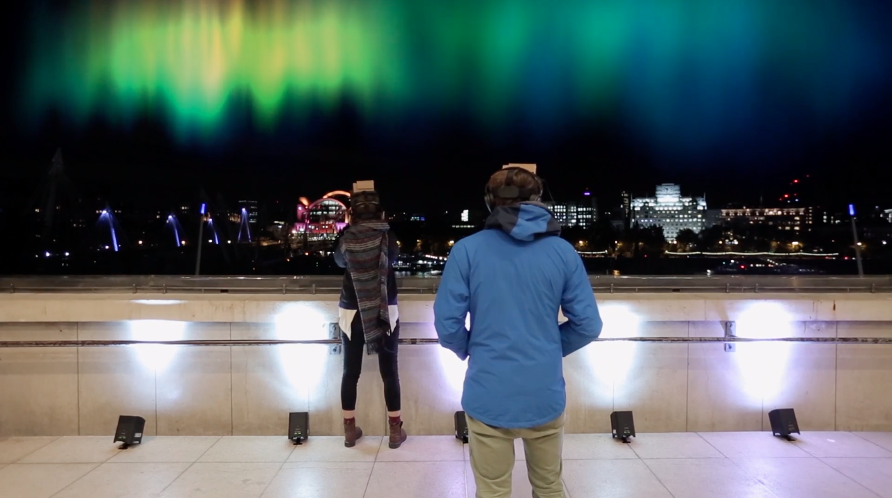 Two people wearing VR headsets stand on a balcony with an Aurora floating in the sky above the London skyline.