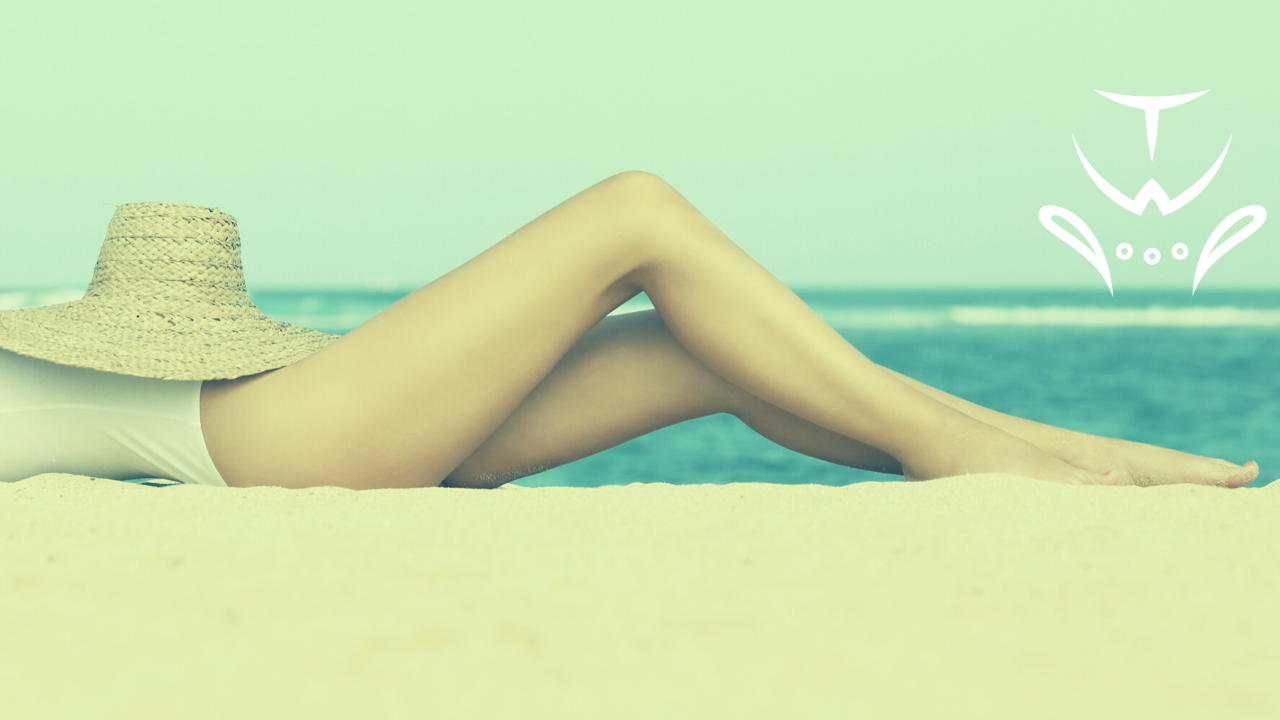 Woman laying on the beach in a bathing suit with a hat over her middle bits.