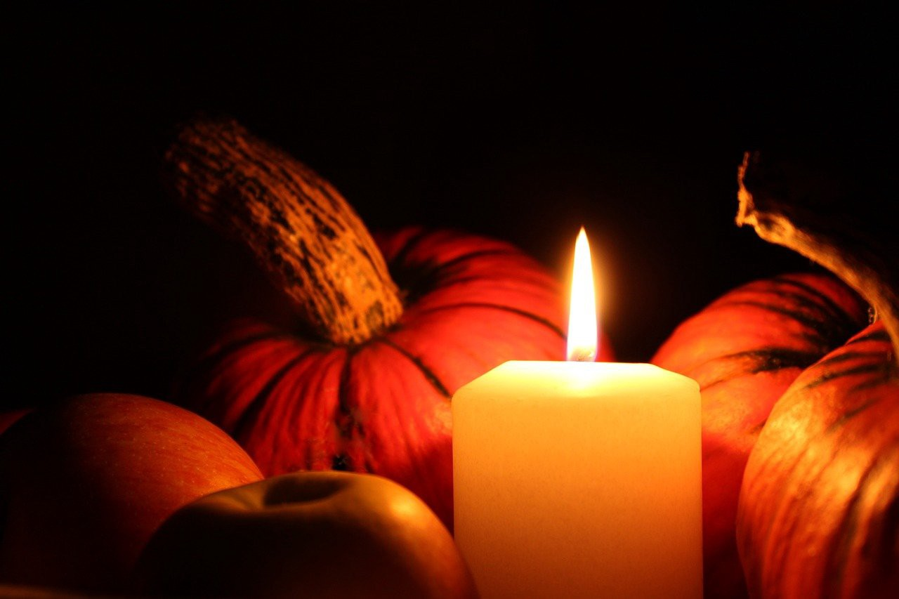Photo of a candle surrounded by pumpkins.