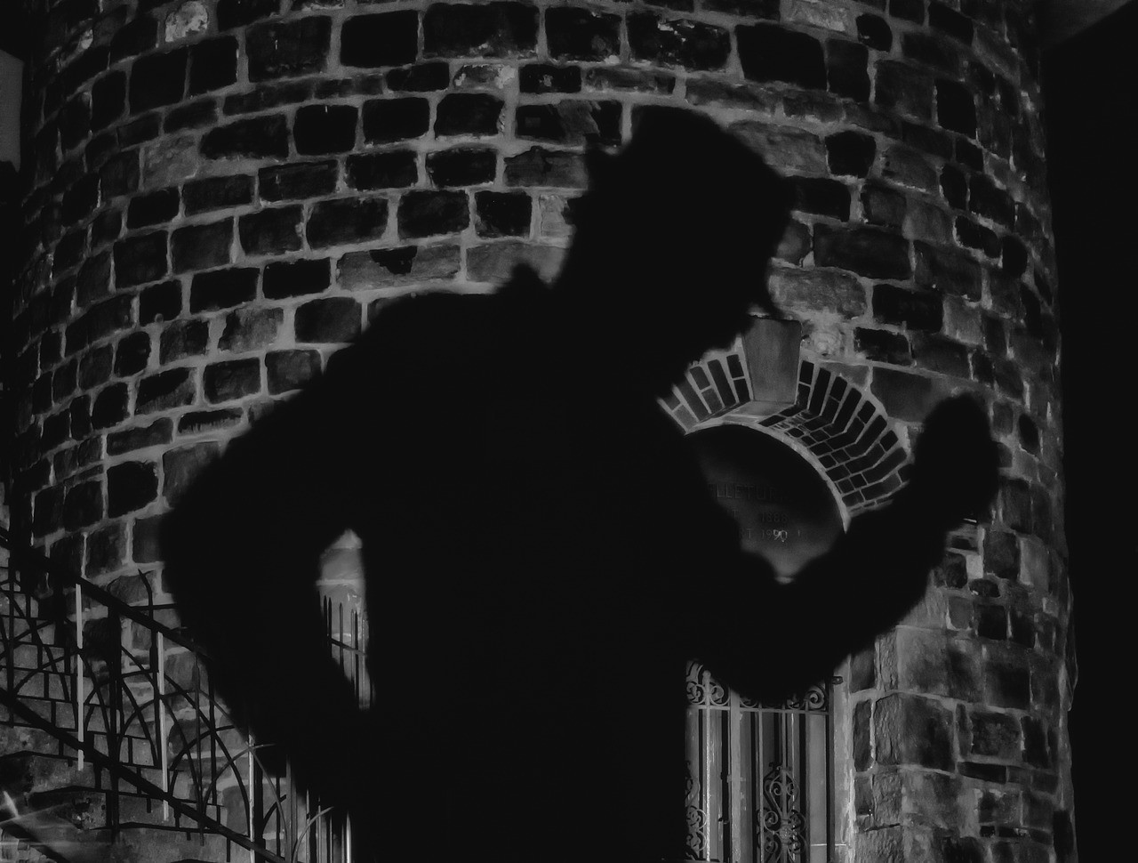 A man's shadow cast upon a brick building