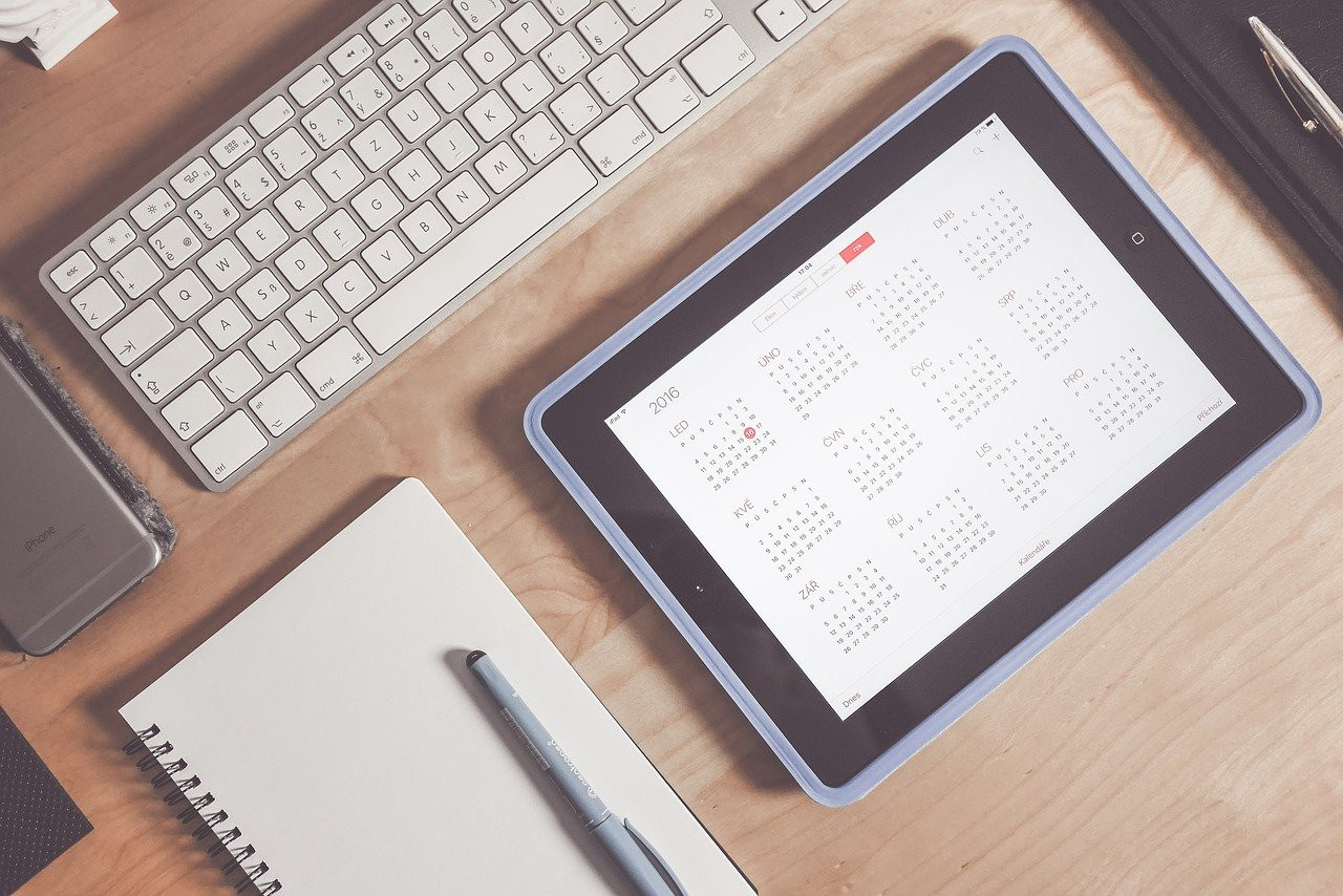 A desktop with a computer keyboard, notepad and pen, and iPad with the calendar pulled up on the screen.