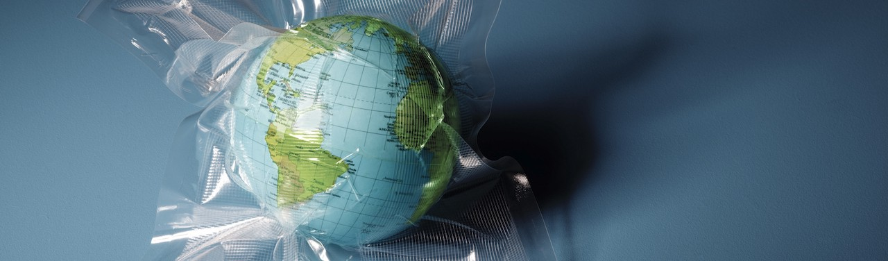 A globe shrink wrapped in plastic on a blue, shadowy background