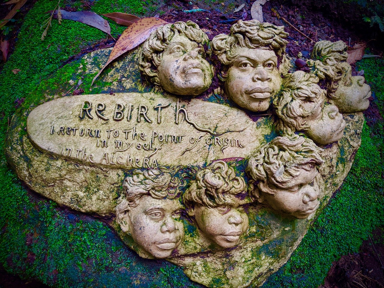 Indigenous Australian faces sculpture on a rock, with a plaque reading: Rebirth, I return to the point of origin in myself.