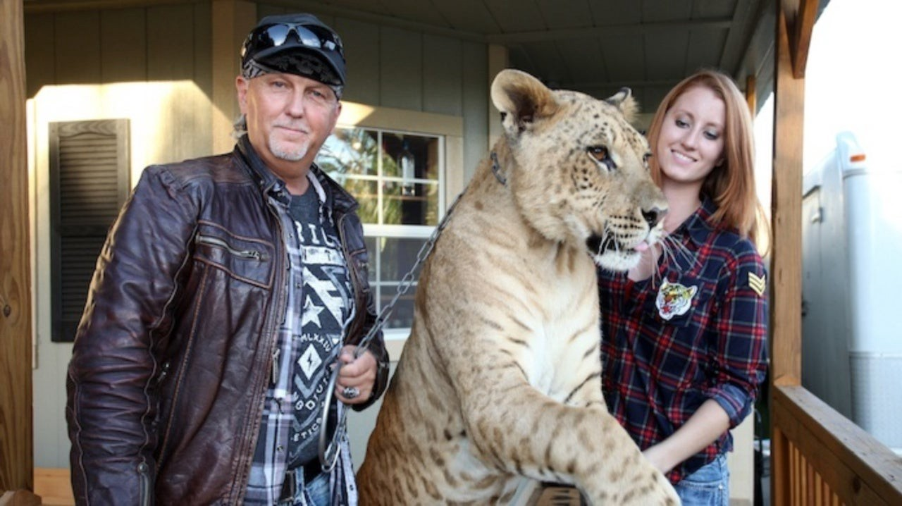 Jeff Lowe and Lauren Lowe holding a big cat on a chain