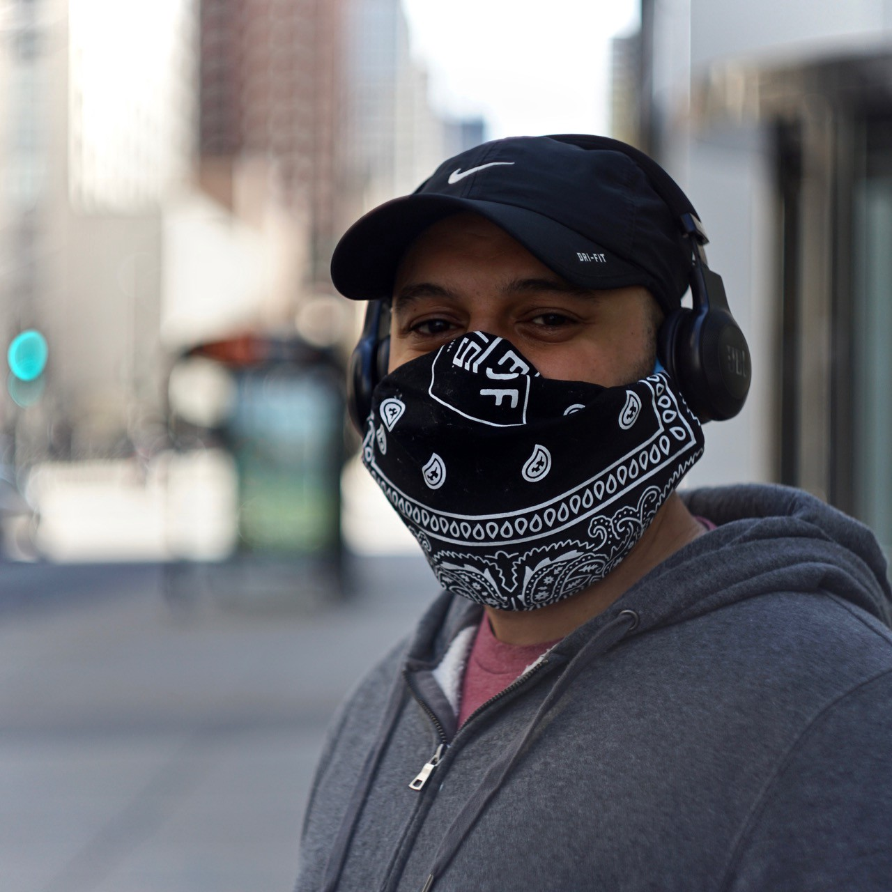 A young man with a hat, headphones, and a black and white mask pauses in downtown Chicago.