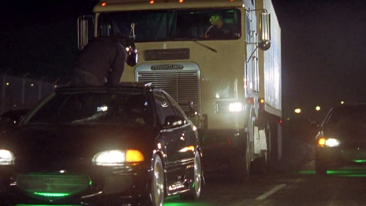 Image from the opening scene of The Fast and the Furious (2001 film). A man is standing on passenger seat of a black Honda Civic sticking out of sun roof as the Honda is trying to out maneuver a white truck behind it.