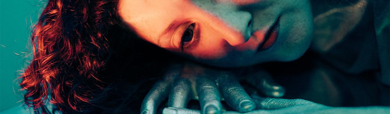 Tightly cropped woman lying down, resting her head on the back of her hand. The shadows are teal; light on her face is orange