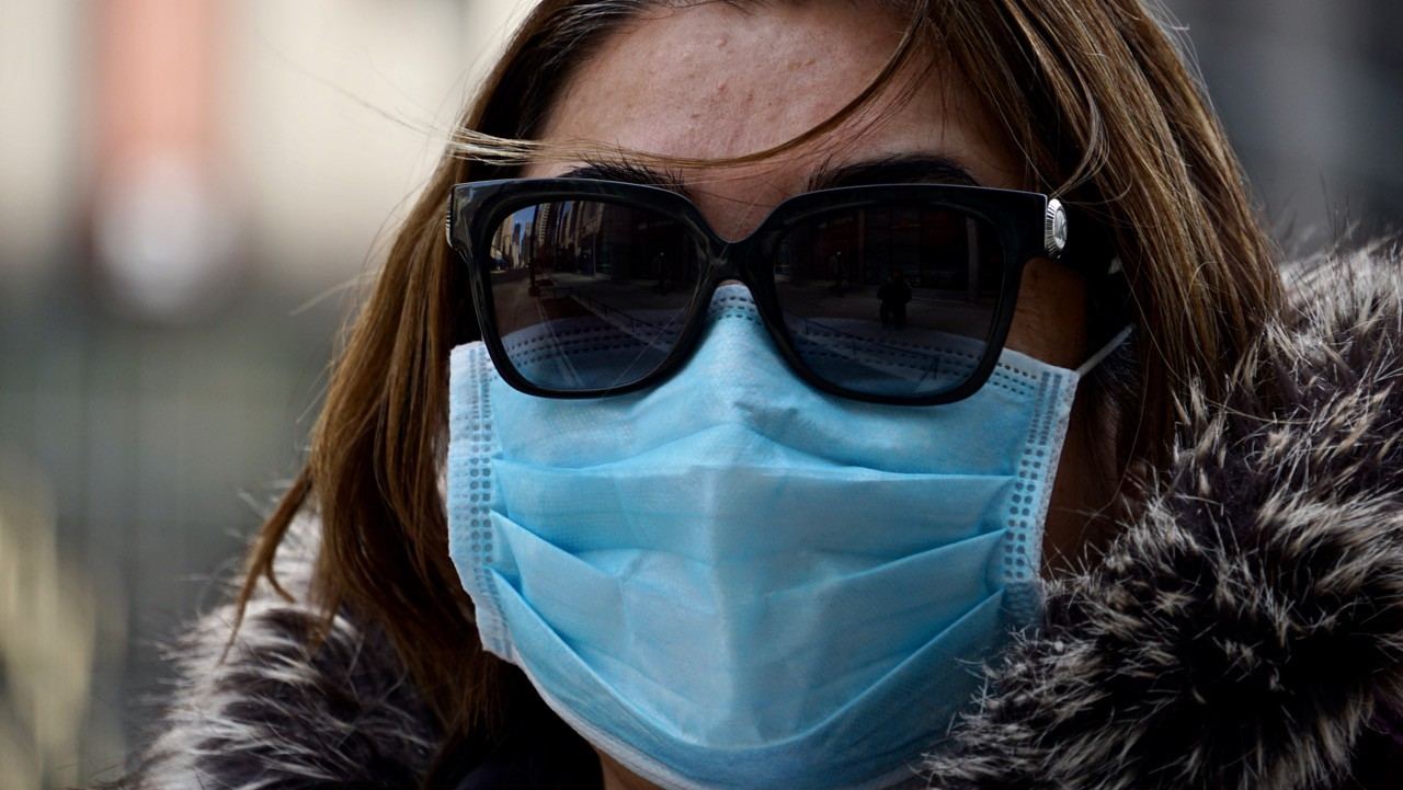 A close up photo of a woman in a blue medical mask with sunglasses that reflect the street and a homeless man.