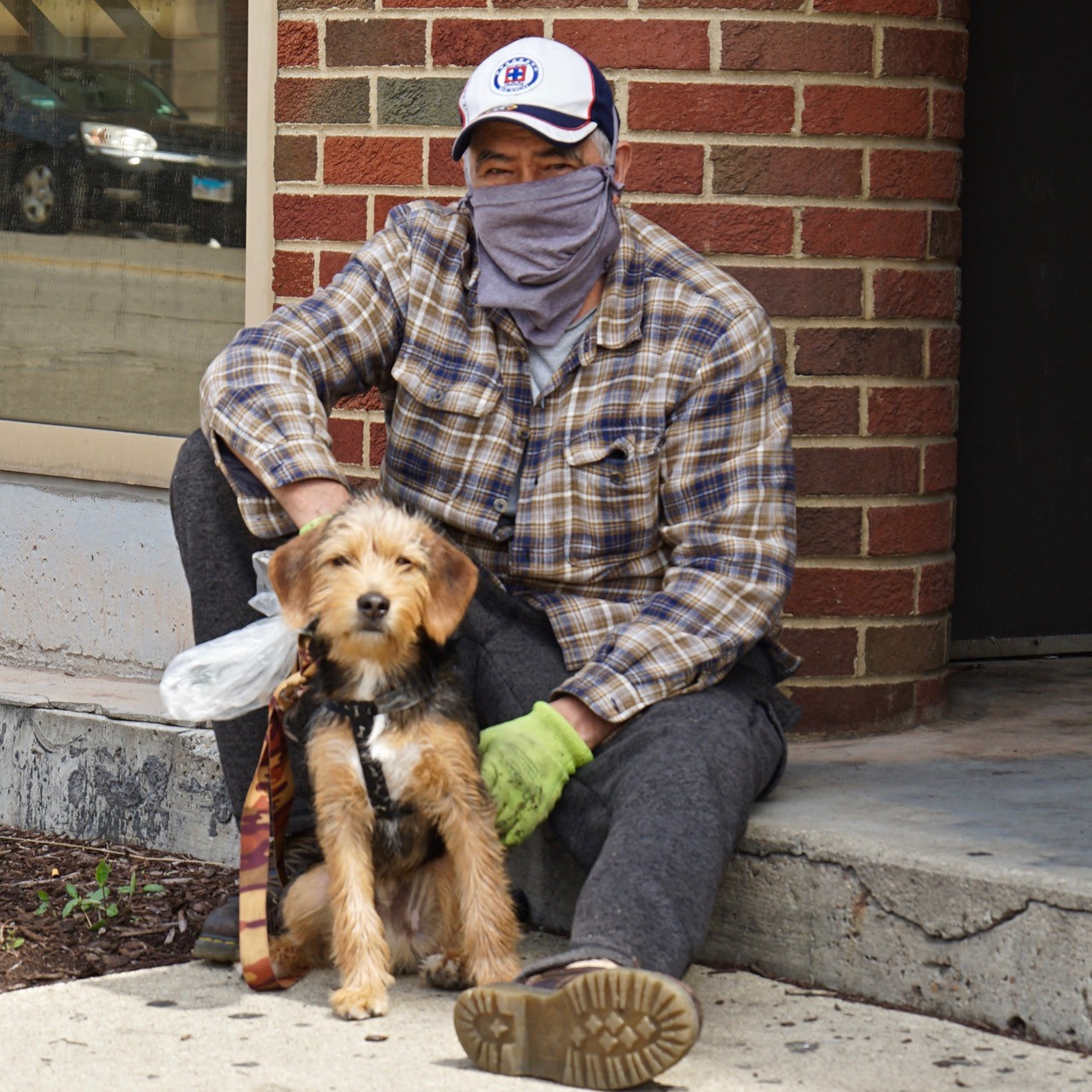 A man in work clothes sits with his dog outside a hospital in Berwyn, IL