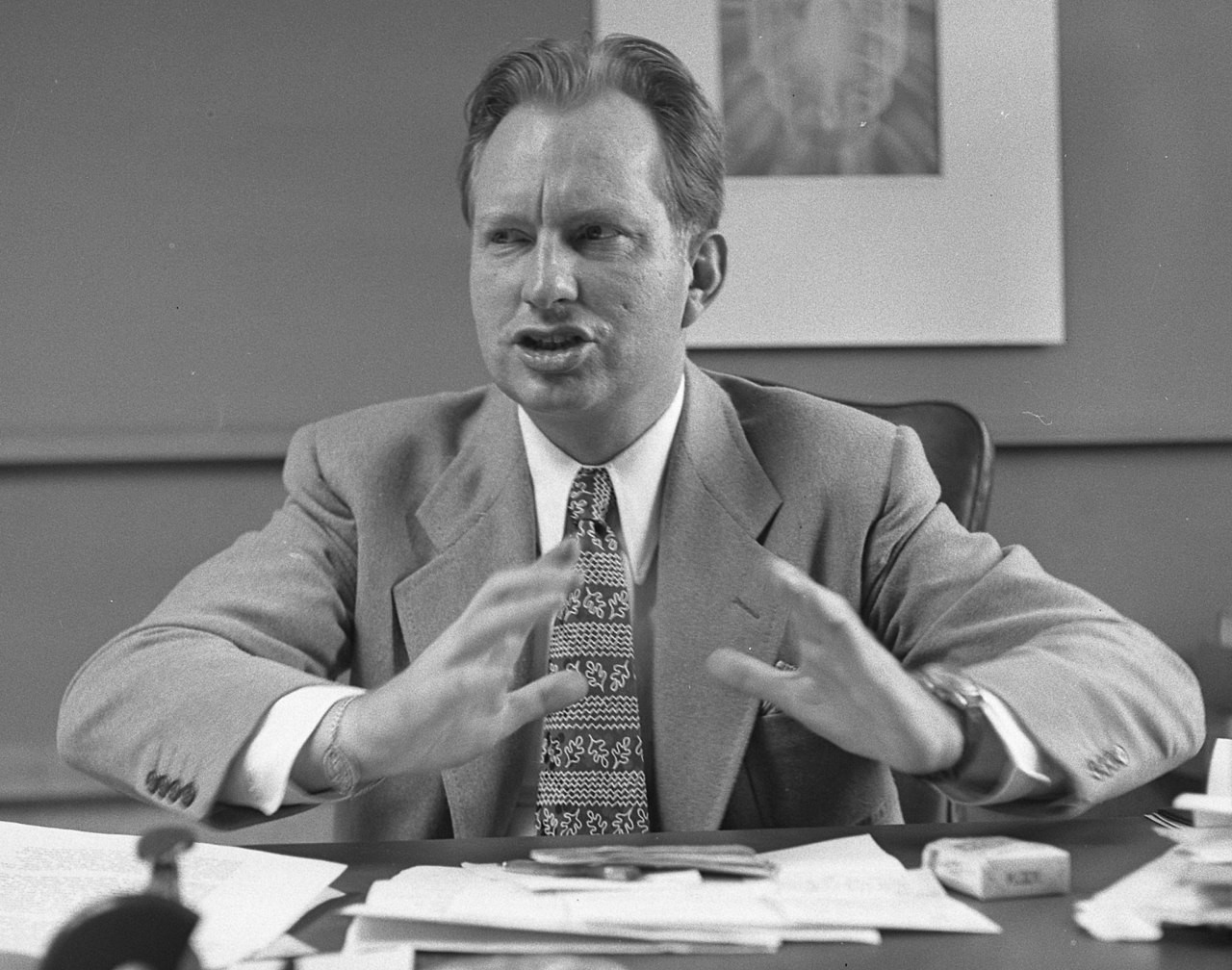 L. Ron Hubbard sitting behind a desk. His arms are hovering above the desk to emphasise a point, and his face is scrunched in mid-sentence.