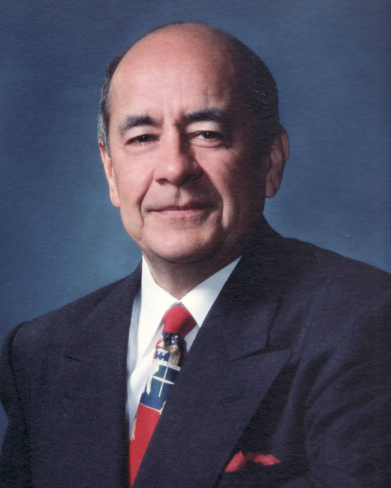 A professional head shot of Fernando Niebla in a suit in front of a blue background
