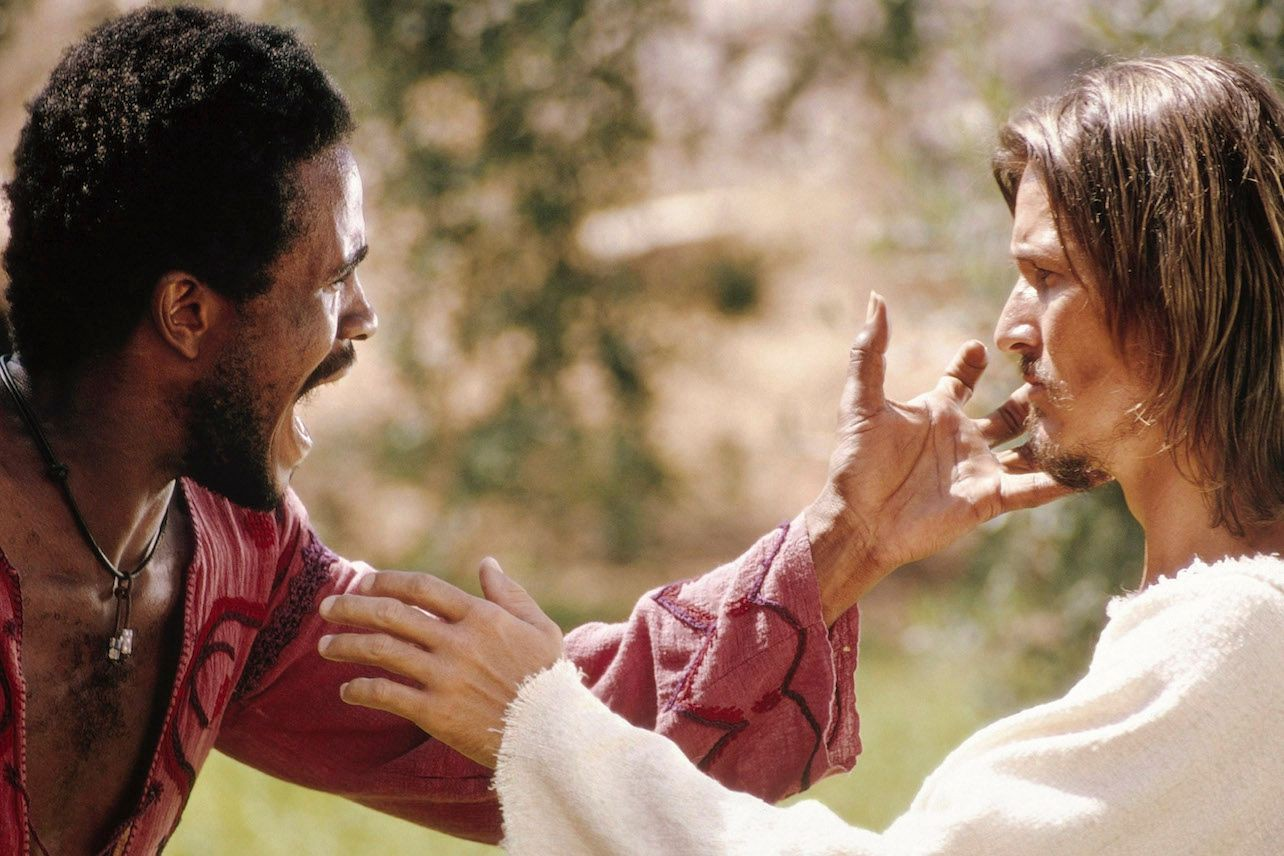 Judas (Carl Anderson), singing intensely, touches Jesus' (Ted Neeley) cheek while Jesus reaches toward his disciple's chest. They are outdoors, but the background is very blurred.