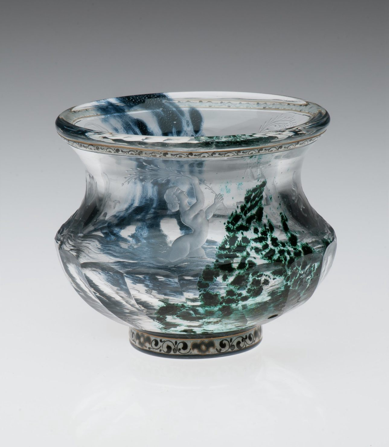 A clear glass vase with intaglio carving and watery patterns of blue and green swirling around a female figure.