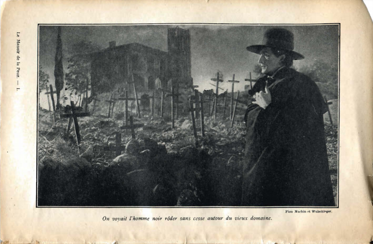 A stranger with a macfarlane and a big hat is seen standing in front of a cemetary of wooden crosses and a church.