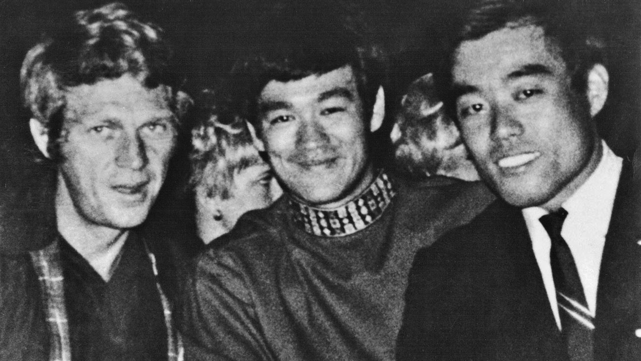 Steve McQueen, Bruce Lee, and karate-traditional weaponry expert Fumio Demura at a 1968 California martial arts exhibition.