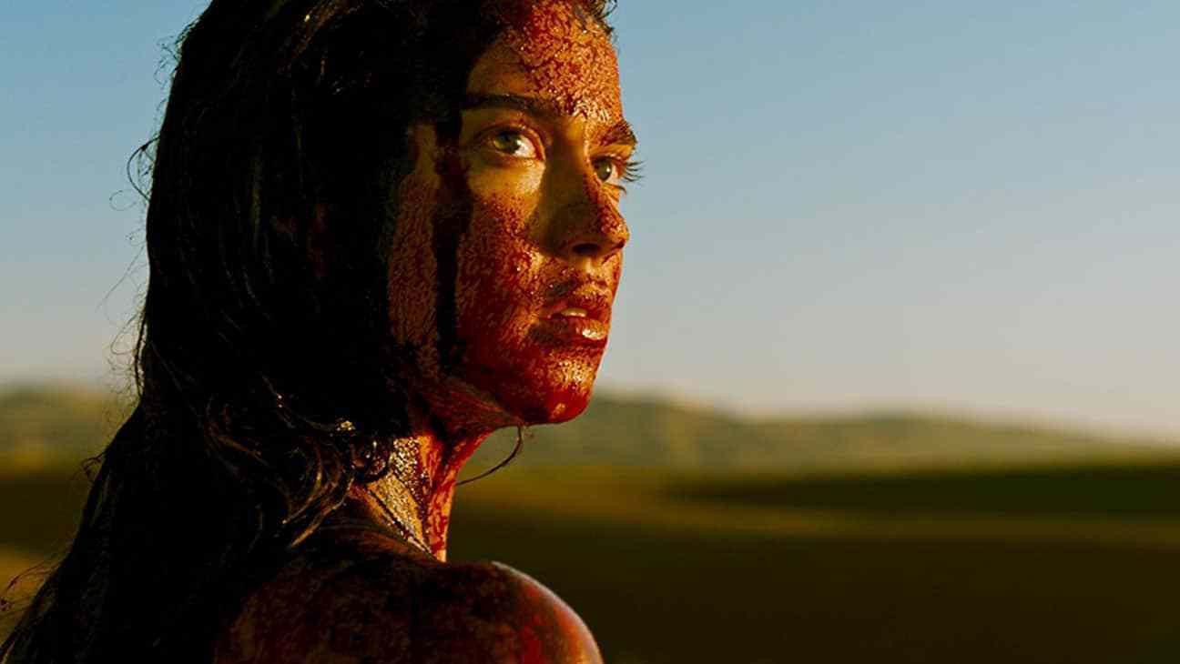 A women covered in blood is seen looking upon her shoulder in a desert.