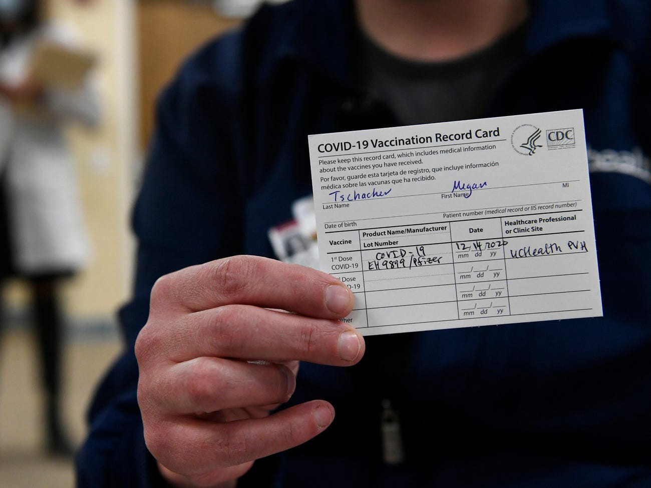 ICU nurse Megan Tschacher shows off her vaccination record card at UC Health Poudre Valley Hospital in Fort Collins, Colorado.