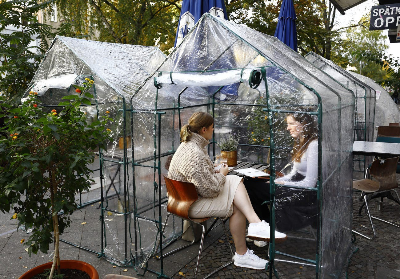 Women sit in a bubble tent at a cafe in Berlin on October 24.