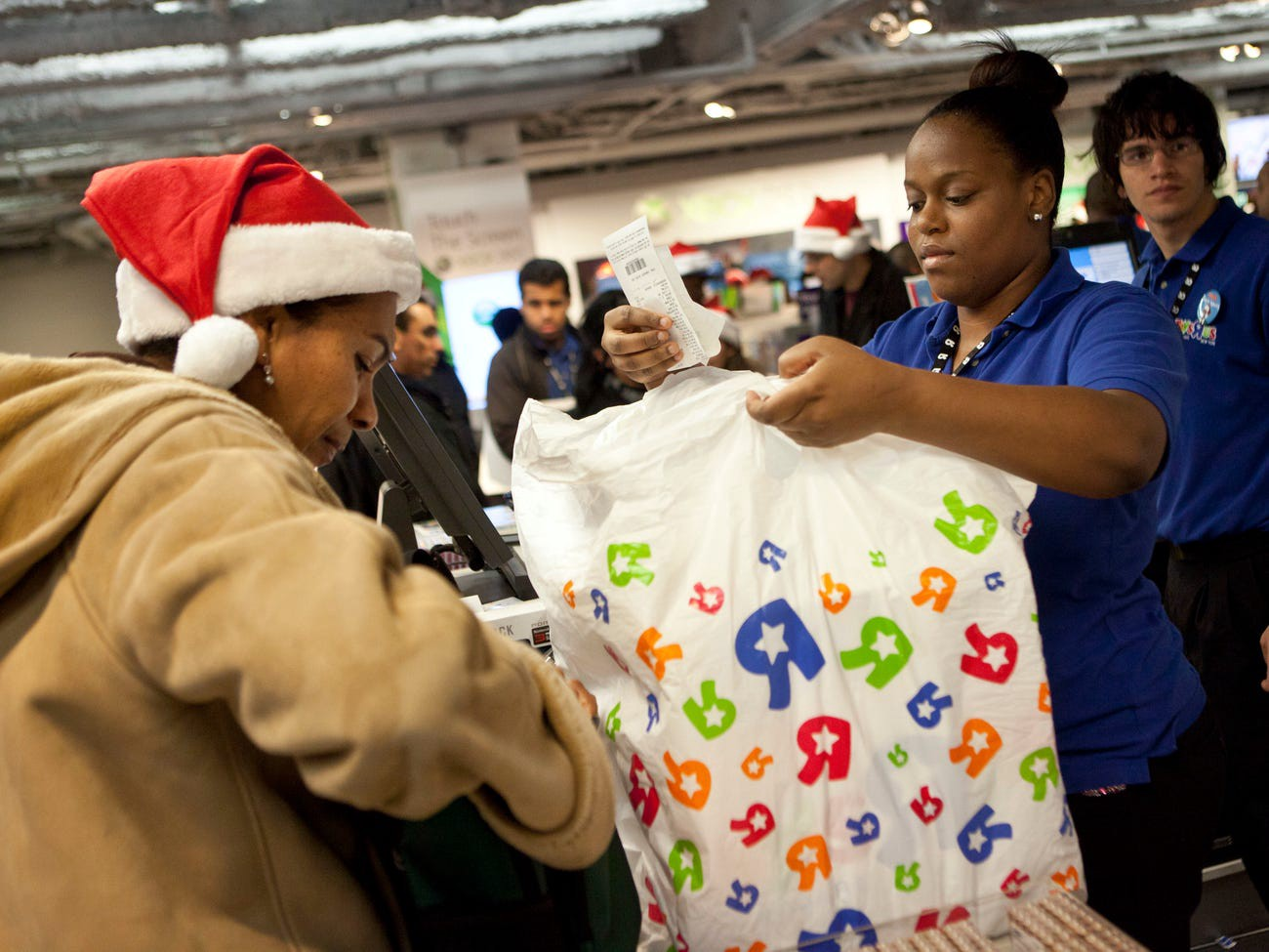 A Toys R Us employee places a receipt in a customer's bag at a New York location in 2011.