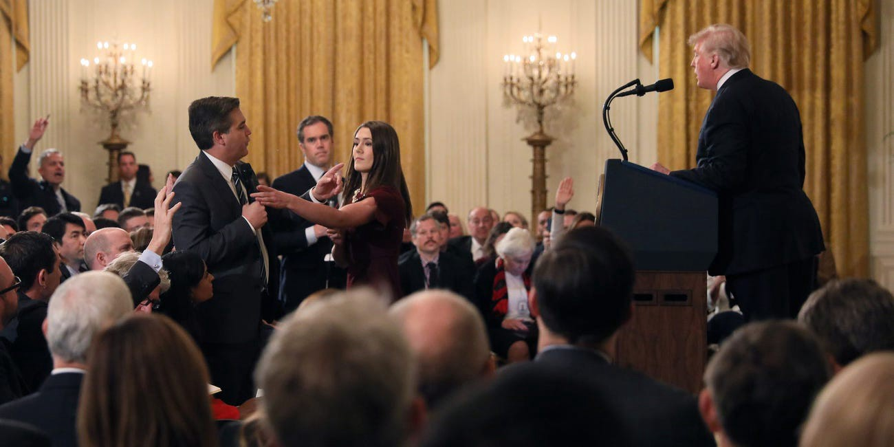 A White House aide attempts to take the microphone from CNN correspondent Jim Acosta during a news conference.