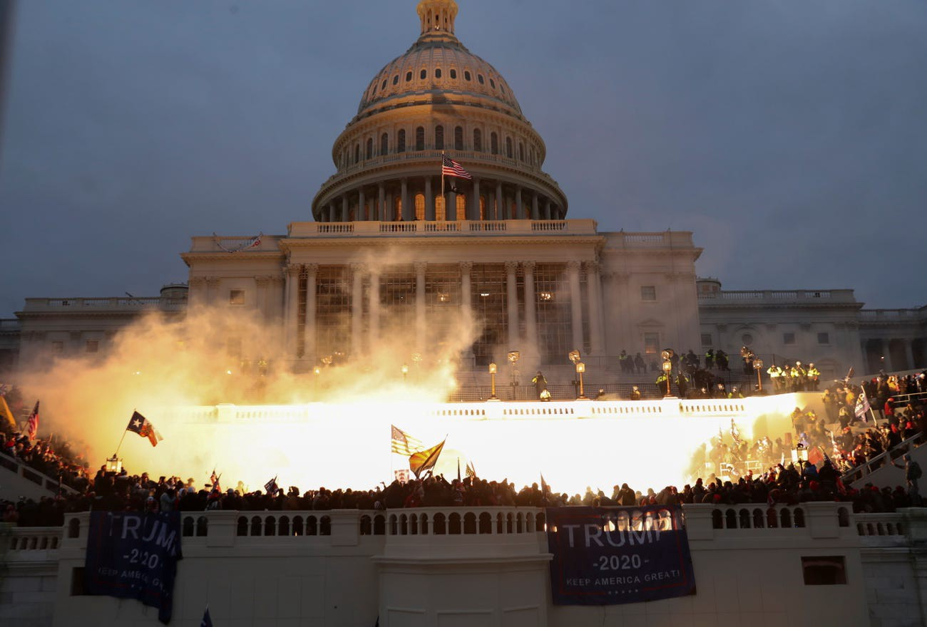 An explosion caused by a police munition is seen while supporters of President Donald Trump gather in front of the Capitol.