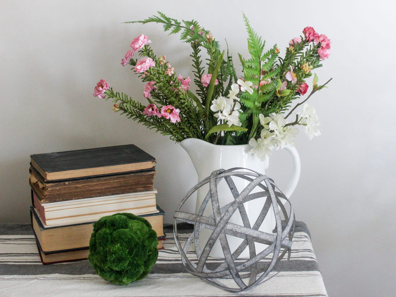 Flowers in a vase next to a stack of books.