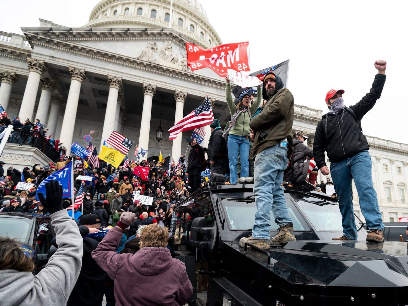 Trump supporters stand on the US Capitol Police armored vehicle as others take over the steps of the Capitol.