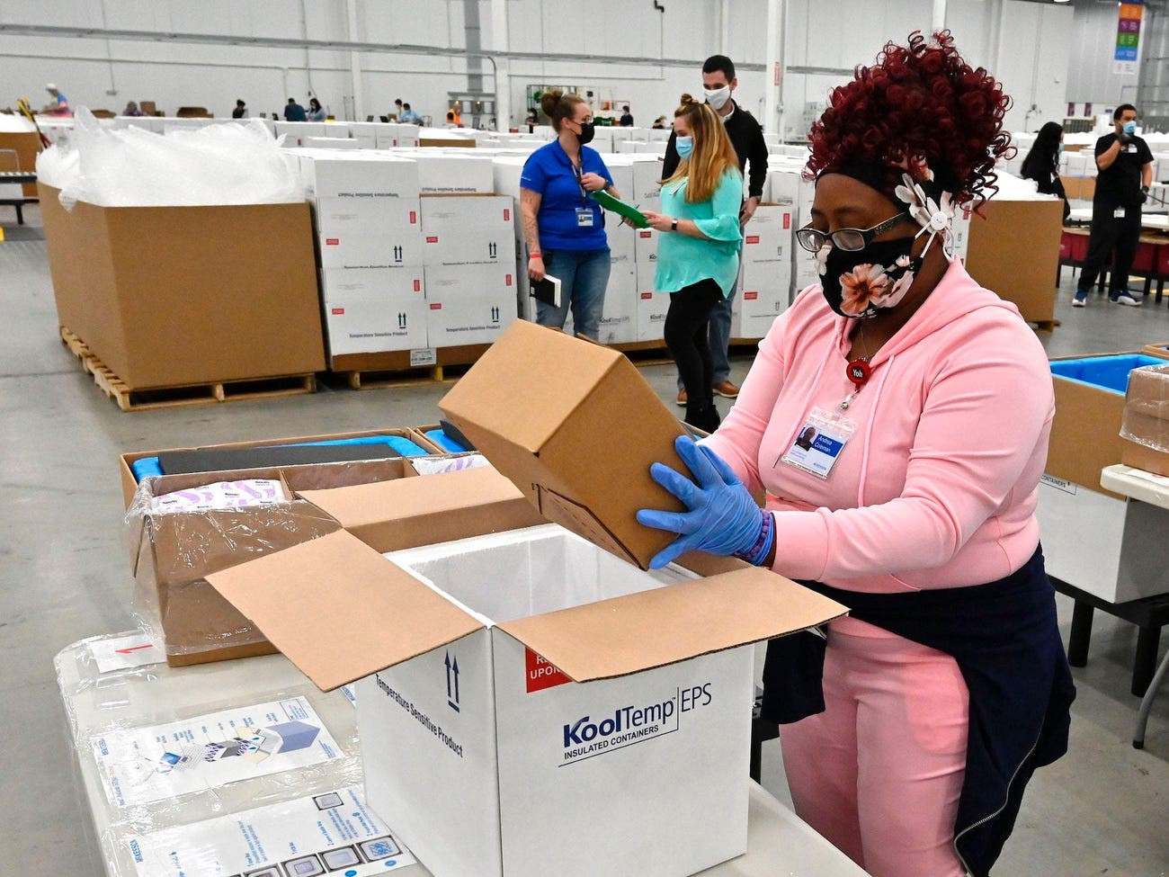 An employee with the McKesson Corp. packs a box of the Johnson & Johnson COVID-19 vaccine into a cooler in Shepherdsville, Kentucky.