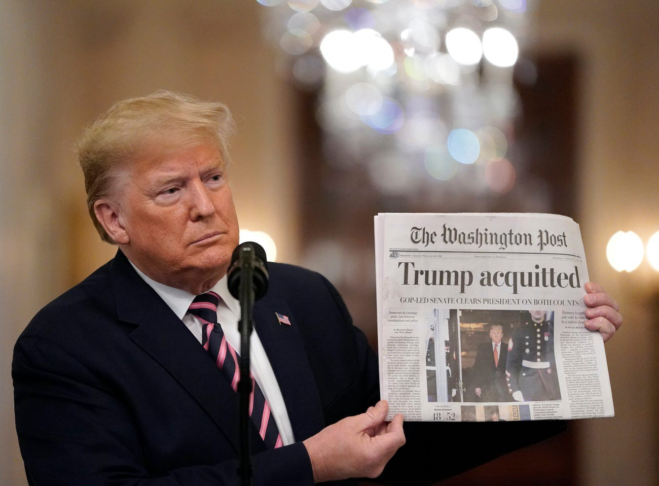 Donald Trump holds a copy of The Washington Post, one day after the Republican-controlled Senate acquitted him.
