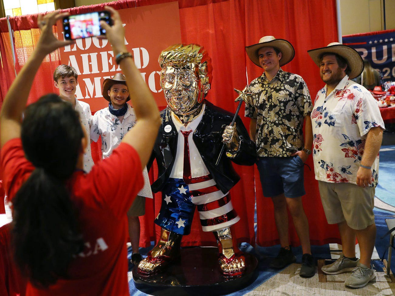 People take a picture with former President Donald Trump's statue on display at CPAC.