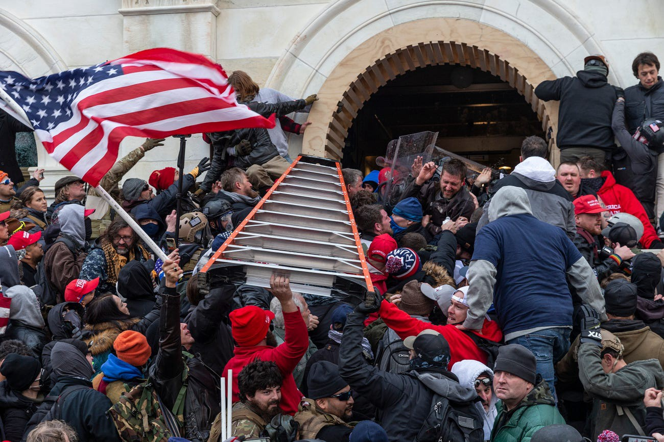Rioters clash with police using big ladder trying to enter Capitol building through the front doors.