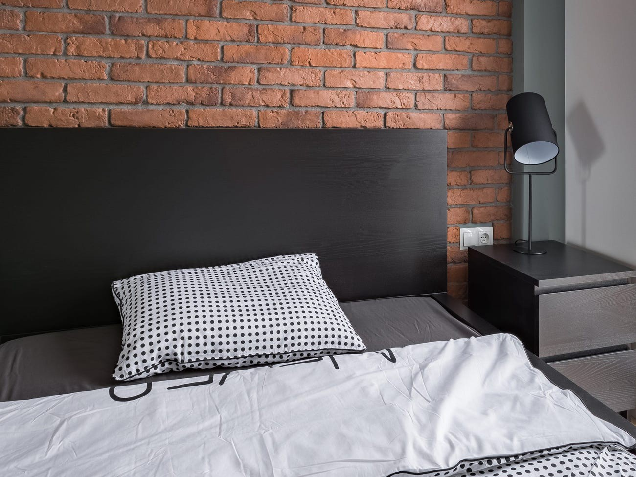 A bed in front of a brick wall.