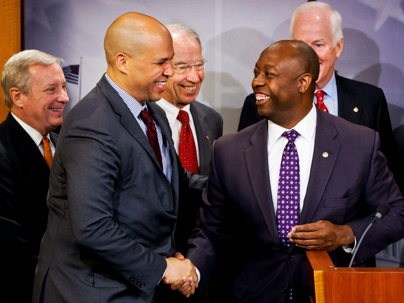 Sen. Tim Scott, right, shakes hands with Sen. Cory Booker during a news conference on Capitol Hill on Oct. 1, 2015.