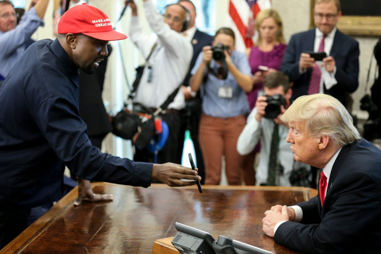 Rapper Kanye West shows a picture of a plane to President Donald Trump at the White House on October 11, 2018.