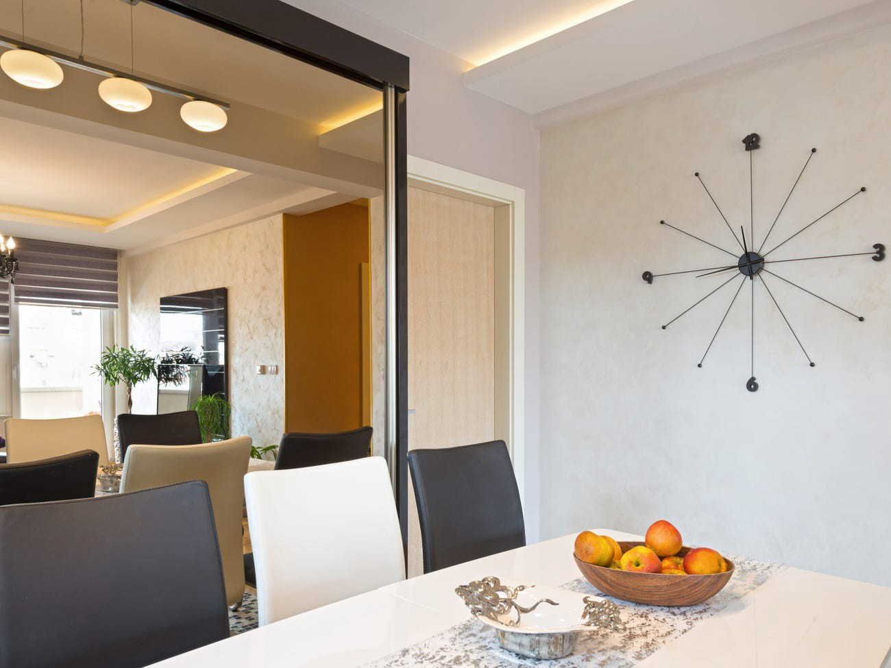 A dining room with a mirrored wall.