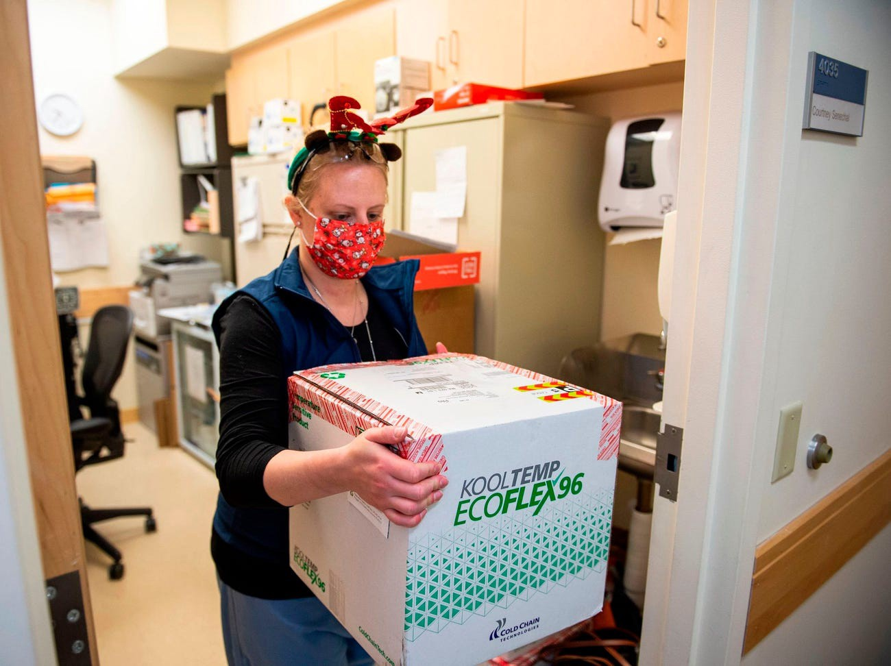 RN Courtney Senechal carries a refrigerated box of Moderna coronavirus vaccines for use at the East Boston Neighborhood Health Center on December 24.
