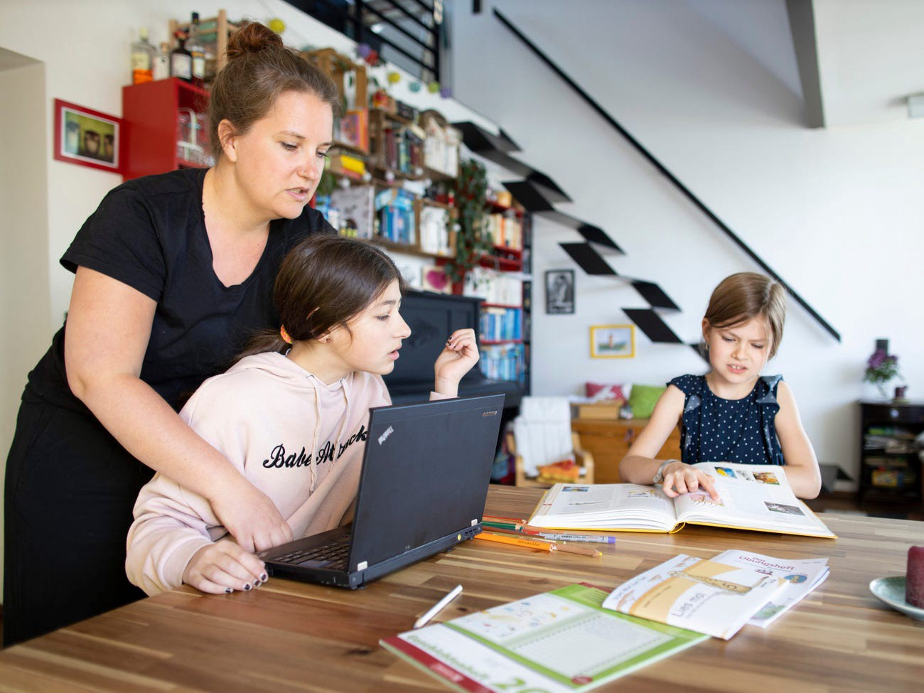 A mother with two children helps doing schoolwork on April 15, 2020.