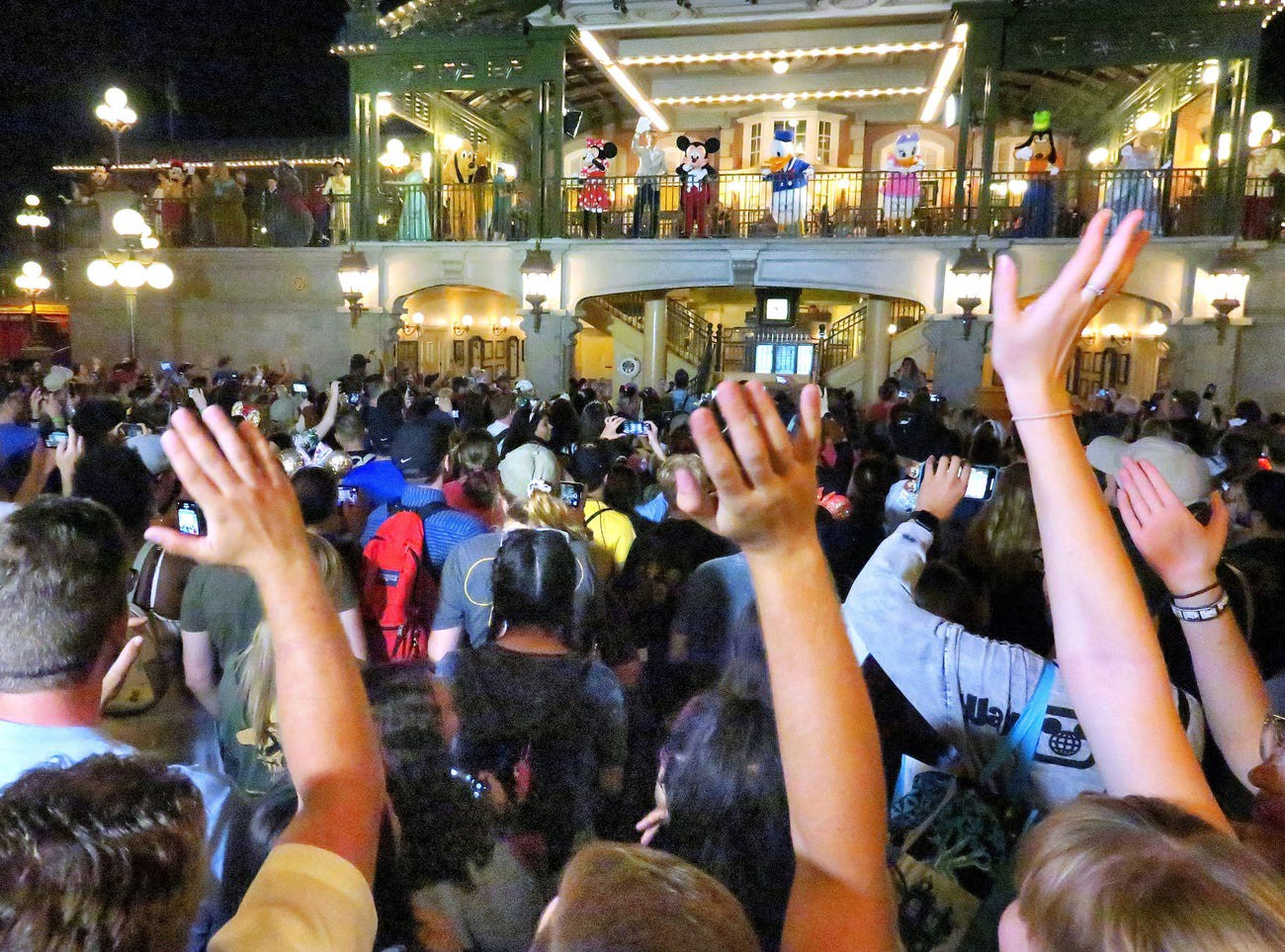 Disney World parkgoers wave goodbye to the theme park in March 2020.
