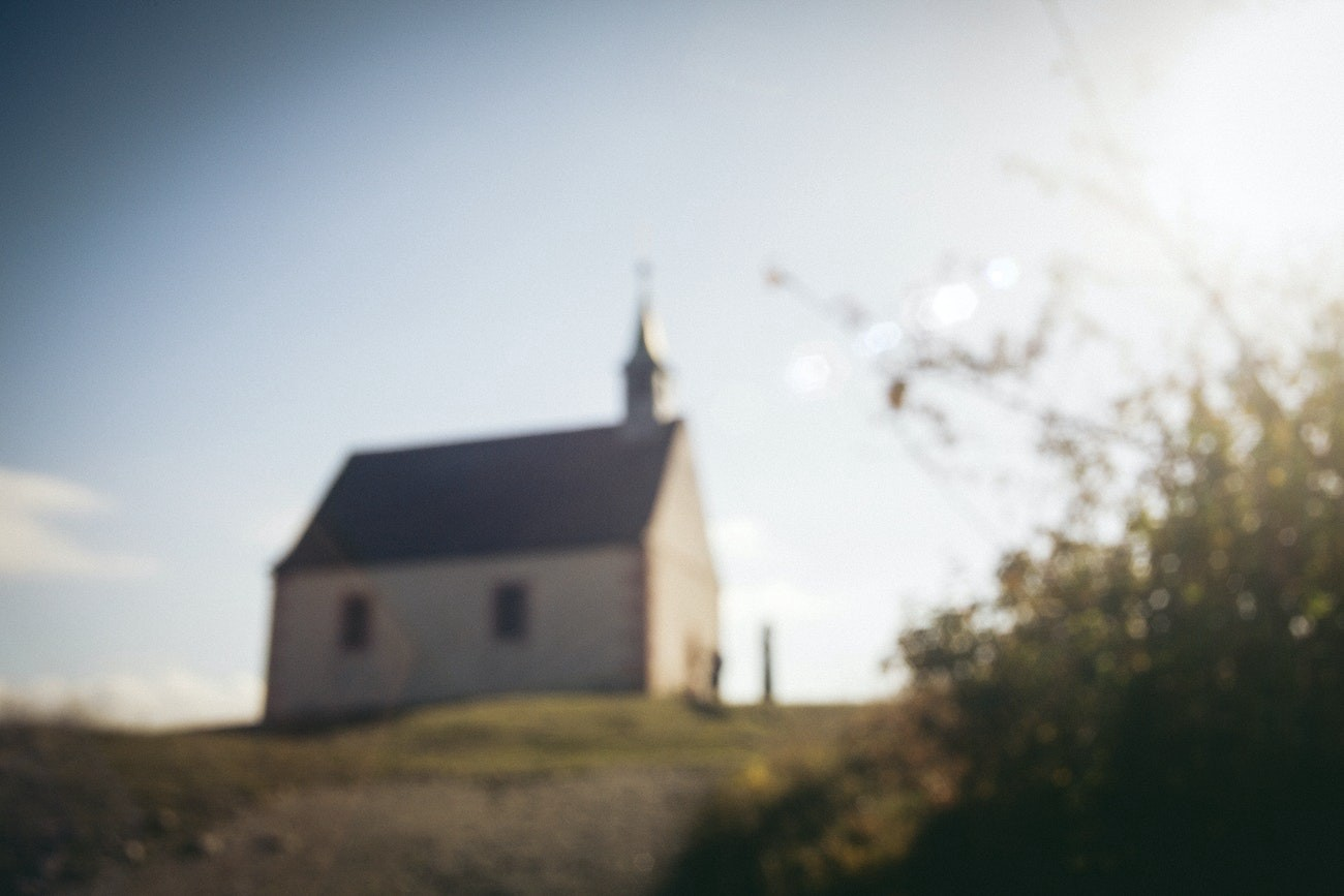 Blurred photo of rural church on grassy hill on sunny day.