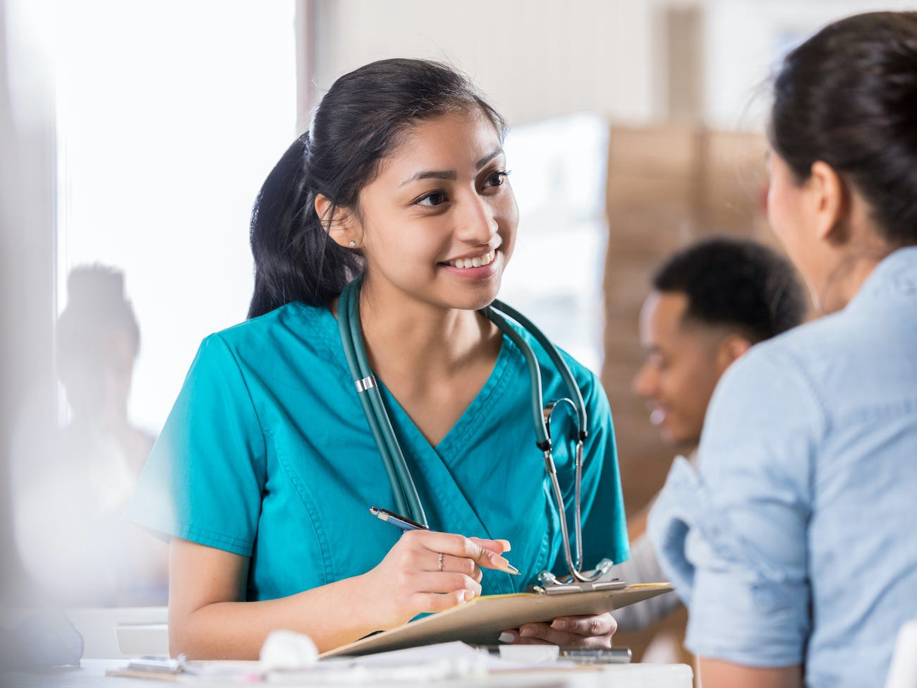 A nurse talking to someone while holding a pen.